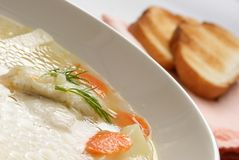 Fish soup. Within white plate close-up, toasts in the background stock photography