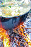Fish soup boils in cauldron. Food background Stock Photography