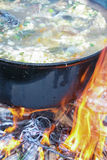 Fish soup boils in cauldron. Food background Stock Photo