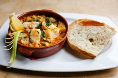 Fish soup with cod. Appetizing Spanish dish All i pebre in a clay plate with lemon and a slice of bread. Potatoes with stock image