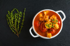 Fish soup with cod, tomato, onion, garlic and thyme in white bowl on black stone background, top view.  Stock Photography