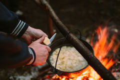 Fish soup cooking on fire in nature and the human hands cut potatoes in a pan. Royalty Free Stock Photo