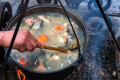 Fish soup. Cooking fish soup in a pot on the fireplace stock image