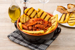 Fish soup with grilled polenta on crock pot Royalty Free Stock Image