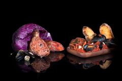 Fish soup, raw fish, scorpion fish, red mullet, crabs. On a black background with reflections stock photography