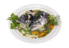 Fish soup from salmon heads. Fish soup in old ceramic mass production plate  is brewed from the heads of Salmon.  Broth with carrots, rice,  potatoes, green Stock Photography