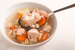 Fish soup with salmon and orge perlé in spoon. On bowl Royalty Free Stock Photo