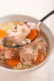 Fish soup with salmon and orge perlé in spoon. On bowl Stock Image