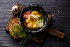 Fish soup with salmon. Potato and carrot in black iron pot on black burned wooden background Royalty Free Stock Photos