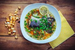 Fish soup with salmon tail. Lemon slice and cut green onion in a plate with croutons and yellow napkin on the wooden table Royalty Free Stock Photos