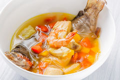 Fish soup with vegetables, shrimps and potatoes in white plate close up Royalty Free Stock Images