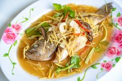 Fish in soy sauce, served on white plate stock image