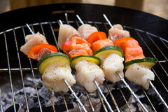Fish spear grilling on barbecue. Delicious fish spear grilling on barbecue royalty free stock photography