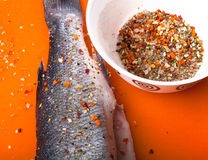 Fish and spices on a plastic cutting board. Fish in the process Royalty Free Stock Image