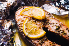 Fish steak baked with lemon and herbs in foil Royalty Free Stock Photos