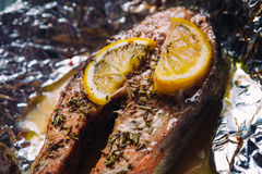 Fish steak baked with lemon and herbs in foil Royalty Free Stock Images