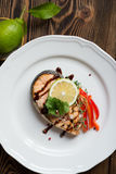 Fish steak salmon. Baked red fish steak salmon on the white plate with vegetable garnish Royalty Free Stock Photo