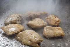 Fish steaks cooking on grill hot plate at a restaurant buffet Stock Images