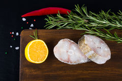 Fish steaks, rosemary, red chili pepper, half a lemon and sea sa Royalty Free Stock Images