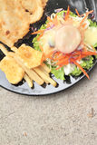 Fish steaks and vegetable salad with french fries. Stock Photography