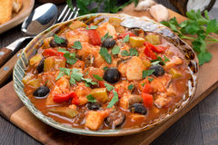 Fish stew with olives in tomato sauce on a plate Royalty Free Stock Images