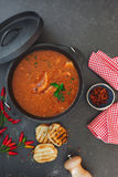 Fish stew with tomatoes in cast iron pot Royalty Free Stock Photos