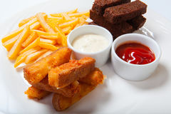 Fish sticks with french fries on a white plate stock images