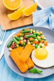 Fish sticks, fried egg and vegetables Stock Photography
