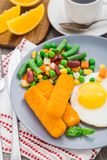 Fish sticks, fried egg and vegetables Stock Photo