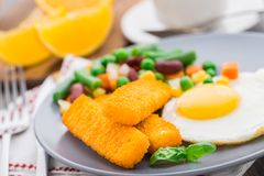 Fish sticks, fried egg and vegetables Stock Photos