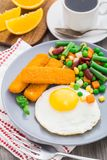 Fish sticks, fried egg and vegetables Royalty Free Stock Photo