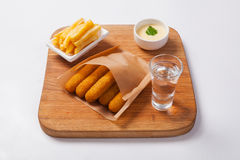 Fish sticks on a wooden board with sauce and fried potatoes Royalty Free Stock Photo