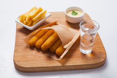 Fish sticks on a wooden board with sauce and fried potatoes Royalty Free Stock Photography