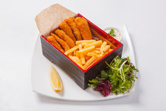 Fish sticks in the wooden box with sauce and fried potatoes Royalty Free Stock Images
