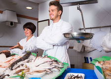 Fish store with two glad sellers Stock Photos