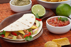 Fish Tacos. Closeup of grilled salmon fish tacos served with guacamole, fresh tomatoes salsa, and tortilla chips Royalty Free Stock Photos
