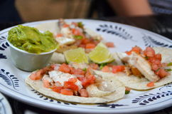 Fish tacos with guacamole. Fresh fish tacos on corn tortillas with pico de gallo, lime, and avocado--a staple of Mexican food Royalty Free Stock Photos