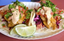 Fish Tacos. A paper plate with two freshly prepared fish tacos and slices of lime stock images