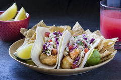 2 fish tacos on plate with chips, lime, and watermelon juice. 2 fried fish tacos in corn tortillas, served with tortilla chips, lime, and a watermelon agua Stock Photos