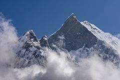 Fish Tail Summit also Machapuchare surrounded by rising clouds. As seen from Machapuchare Base Camp in the Himalayas stock images