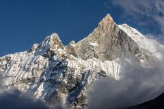 Fish Tail Summit also Machapuchare surrounded by rising clouds, Himalayas royalty free stock photos