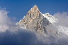 Fish Tail Summit Machapuchare surrounded by rising clouds in Himalayas. Annapurna Base Camp trekking. Nepal royalty free stock photo