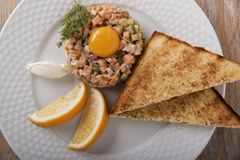 Fish tartare salmon with yolk and toast on a plate Stock Photos
