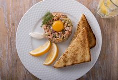 Fish tartare salmon with yolk and toast on a plate Stock Photography