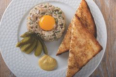 Fish tartare with yolk and toast on a plate Royalty Free Stock Images