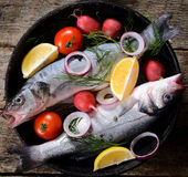 Fish time. Bass fish in the old pan on the wooden background Stock Images
