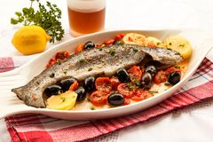 Fish with tomatoes and olives. Cooked in the oven. Mediterranean influences for healthy cooking. Fresh Trout Stock Photos