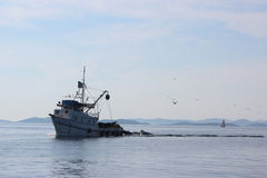 Fish trawler coming in a dusk Royalty Free Stock Photo