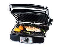 fish and vegetables on electric grill stock images
