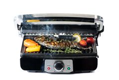 Fish and vegetables on electric grill royalty free stock photography